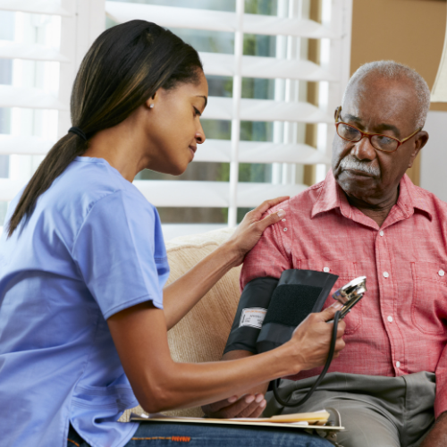 Black nurse taking blood pressure of older Black male.