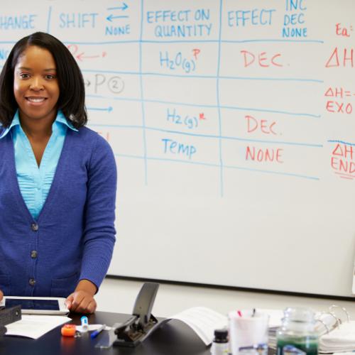 Black Female Educator standing in front of whiteboard.